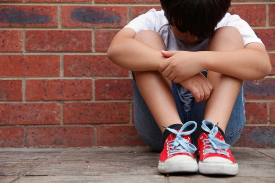 Young boy sitting on the ground staring at his feet